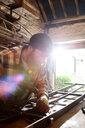 Blacksmith hammering metal on workbench in blacksmiths shop - CUF44127