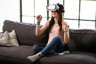 Teenage girl on sofa looking through virtual reality headset - CUF44142