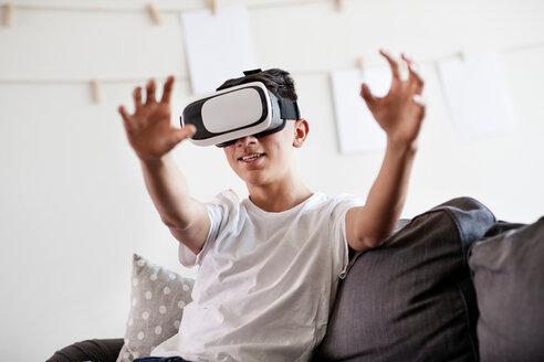 Teenage boy on sofa looking through virtual reality headset and reaching out - CUF44145