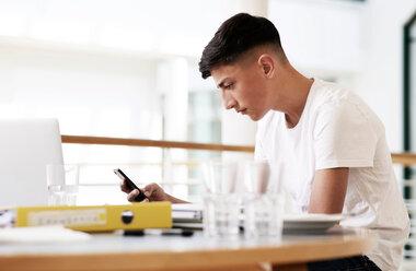 Teenage schoolboy at classroom desk looking at smartphone - CUF44151