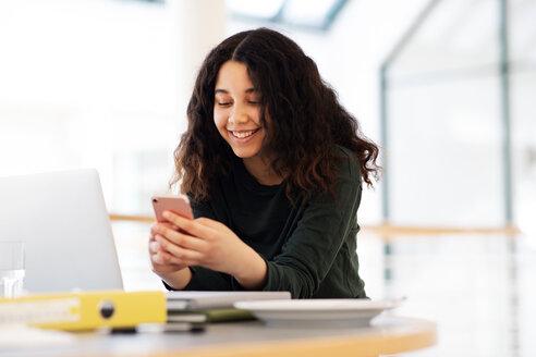 Teenage schoolgirl at classroom desk looking at smartphone - CUF44154