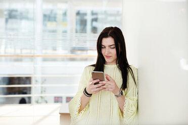 High school girl in school lobby looking at smartphone - CUF44163