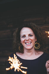 Laughing woman holding sparklers - HMEF00013