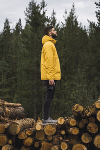 Man with camera standing on stack of wood - KKAF02380