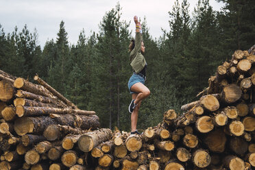 Young woman standing on one leg on stack of wood - KKAF02383