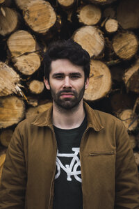 Portrait of young man in front of of stack of wood - KKAF02386