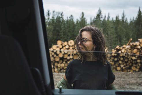 Young woman standing beside car next to stack of wood - KKAF02389