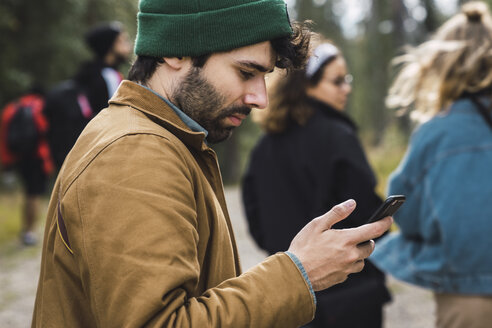 Man checking cell phone outdoors with friends in background - KKAF02392