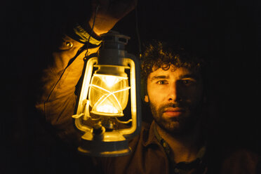 Portrait of man holding storm lantern in the dark - KKAF02401