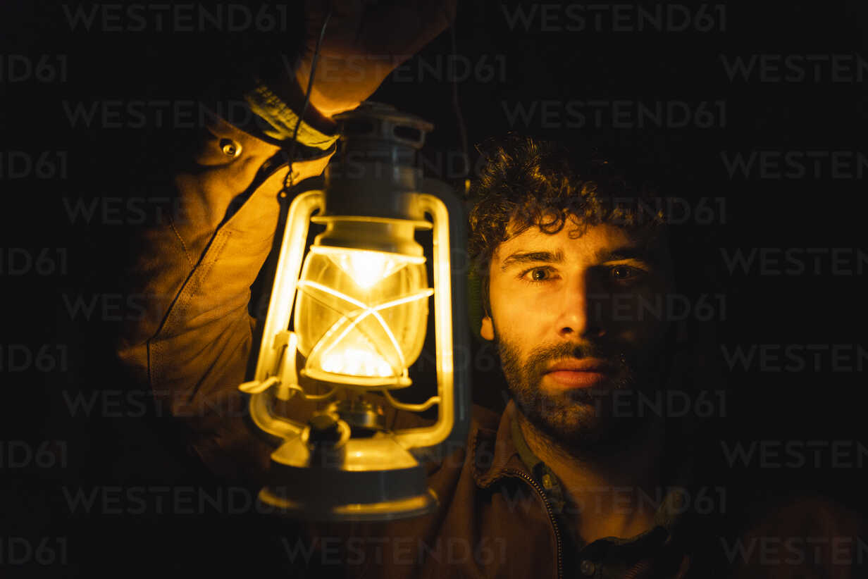 Portrait of man holding storm lantern in the dark - KKAF02401 - Kike Arnaiz/Westend61