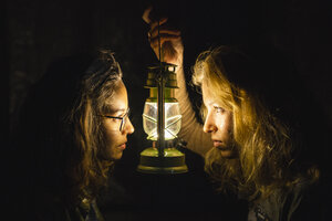 Two young women with storm lantern in the dark facing each other - KKAF02404