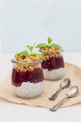 Two glasses of chia pudding with coconut milk, red fruit jelly and peanut granola topping - JUNF01360