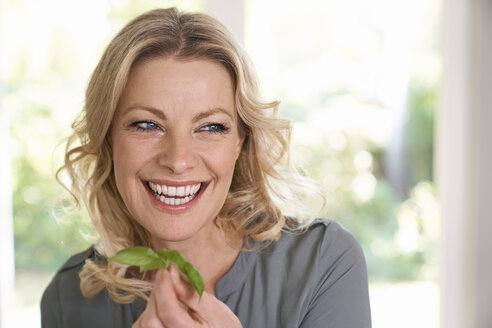 Portrait of smiling woman holding basil in kitchen - PDF01727