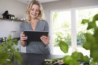 Smiling woman using tablet in kitchen - PDF01733