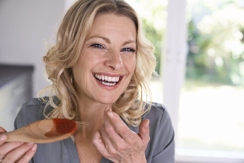 Portrait of happy woman tasting tomato sauce from cooking spoon - PDF01736