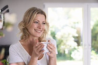 Portrait of smiling woman drinking coffee in kitchen - PDF01739