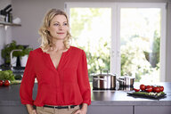 Confident woman wearing red blouse standing in kitchen - PDF01742