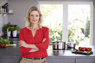 Portrait of confident woman wearing red blouse standing in kitchen - PDF01745