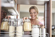 Smiling woman in kitchen taking jar from kitchen cabinet - PDF01754