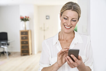 Smiling woman using cell phone at home - PDF01763