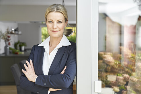 Portrait of confident businesswoman leaning against French door at home - PDF01769