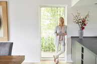 Portrait of happy woman standing at French door using tablet at home - PDF01775