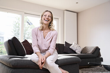 Portrait of laughing woman sitting on couch at home - PDF01778
