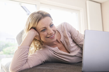 Smiling woman lying on couch using tablet at home - PDF01784