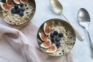 Bowls of porridge with sliced figs, blueberries and dried berries - JUNF01384