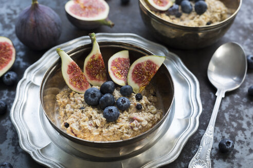 Bowl of porridge with sliced fig, blueberries and dried berries - JUNF01387
