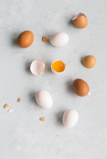 Whole and opened white and brown eggs on light ground - JUNF01406