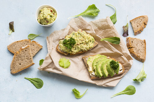 Slices of bread with sliced avocado and avocado cream on brown paper - JUNF01409