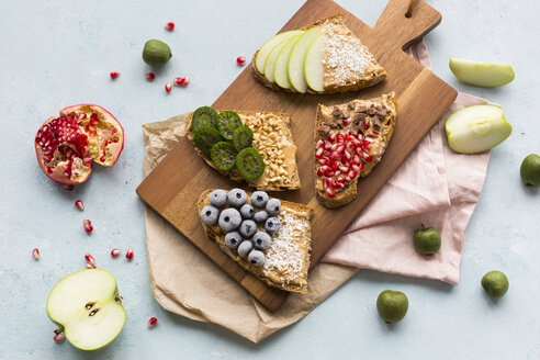 Bread slices with various toppings on wooden board - JUNF01415