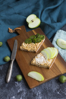 Bread slices with various toppings on wooden board - JUNF01421