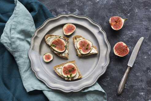 Buttered slices of bread with sliced figs on tin plate - JUNF01424