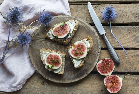 Buttered slices of bread with sliced figs on wooden plate - JUNF01427