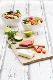 Watermelon salad with feta, cucumber, mint and lime dressing on white wood - LVF07449