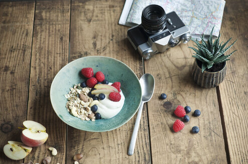 Breakfast bowl with granola, yogurt, nuts, apple, raspberry, blueberry on wood - ASF06236