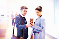 Young businesswoman and man in airport looking at smartphone - CUF44224