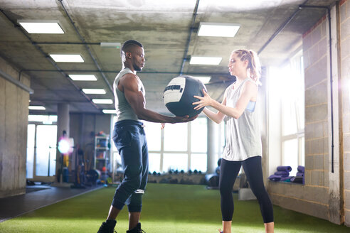 Trainer handing over medicine ball to female client in gym - CUF44251