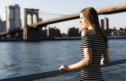 USA, New York, Brooklyn, woman wearing striped dress standing in front of East River by sunset - GIOF04557