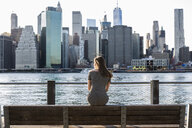 USA, New York, Brooklyn, back view of woman sitting on bench in front of East River and skyline of Manhattan - GIOF04569