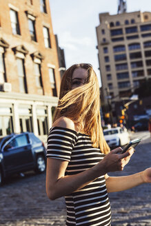 USA, New York, Brooklyn, Dumbo, woman with cell phone crossing the street - GIOF04578