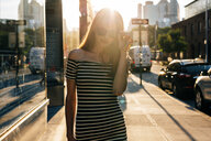 USA, New York, Brooklyn, Dumbo, young woman wearing striped dress and sunglasses at sunset - GIOF04590