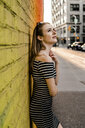 USA, New York, Brooklyn, Dumbo, young woman leaning against yellow wall looking up - GIOF04596