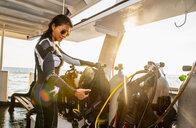 Woman checking dive gear, Tubbataha Reefs Natural Park, Sulu Sea, Philippines - CUF44284