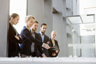 Businesswomen and men pointing at architectural model in office - CUF44317