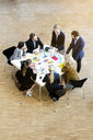 Businesswomen and men in office atrium discussing design swatches on table, high angle view - CUF44320