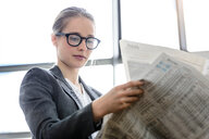 Businesswoman reading newspaper in office - CUF44338