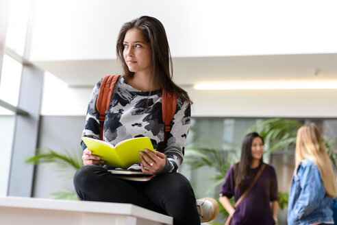Young female university student reading book in university lobby - CUF44350